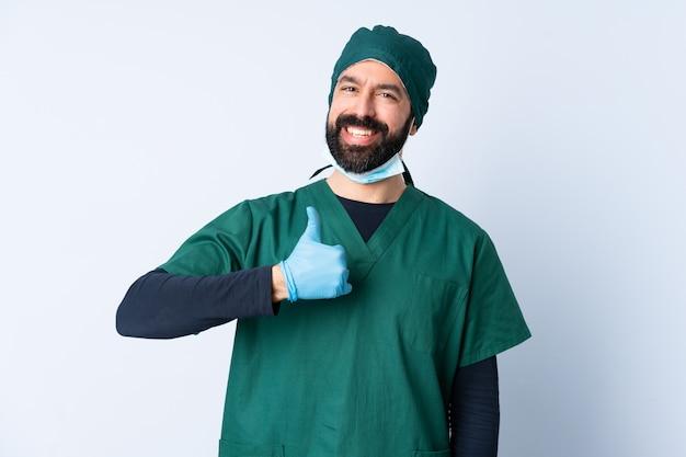 Chirurga mężczyzna w zieleń mundurze nad odosobnioną ścianą daje aprobata gestowi