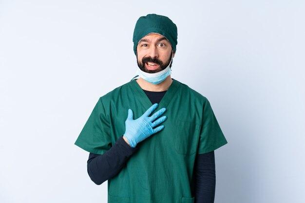 Chirurga mężczyzna w zieleń mundurze nad odosobnioną ścianą wskazuje ja