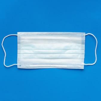 Chirurgiczna maska medyczna ochronna na niebieskim tle. medyczny bandaż oddechowy na ludzką twarz. koncepcja kwarantanny koronawirusa, wybuch pandemii. skopiuj miejsce, kwadratowy obraz dla mediów społecznościowych. zbliżenie.