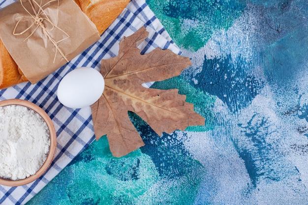 Chleb bagietkowy, mąka, jajko i mleko na ściereczce, na niebiesko.