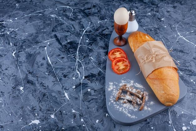 Chleb bagietkowy, pokrojone warzywa, jajko gotowane na pokładzie na niebiesko.