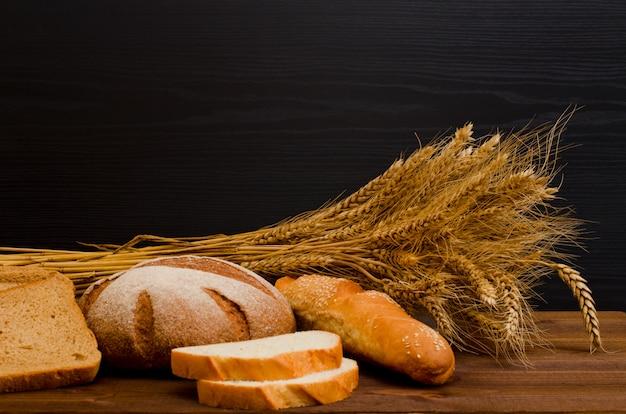 Chleb biały i żytni, bochenek, snop na drewnianym stole, czarne tło, miejsca na tekst