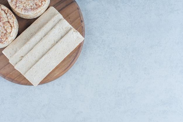 Chleb chrupki i dwa stosy wafli ryżowych na pokładzie na marmurze.