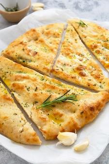 Chleb czosnkowy foccacia. świeżo upieczony płaski chleb czosnkowy, oliwa z oliwek i zioła.