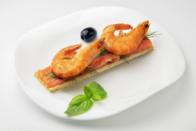 Chleb dietetyczny z plastrami czerwonej ryby i krewetkami z gałązką koperku, oliwki na białym talerzu, zdrowa żywność