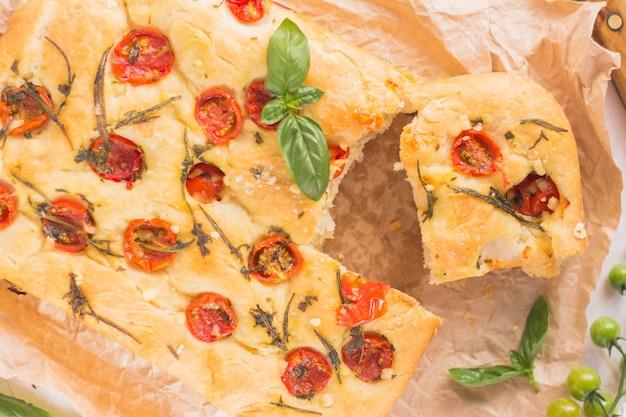 Chleb focaccia z pomidorami i bazylią rozmarynową na drewnie na beżowym brązowym papierze