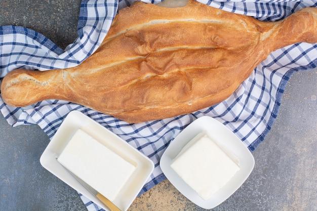 Chleb i dwa talerze sera na obrusie.