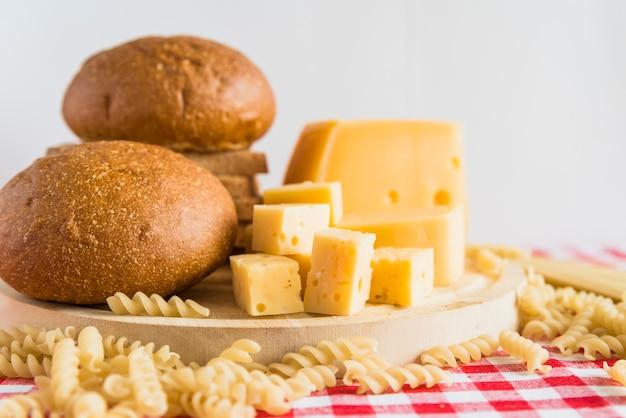 Chleb i ser na talerzu blisko rozrzuconego makaronu