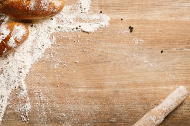 Chleb i toczna szpilka na drewnianym tle