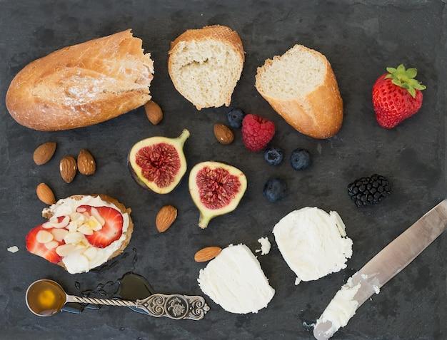 Chleb, kozi ser, migdały, miód i jagody na ciemnej powierzchni
