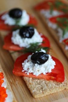 Chleb krakersowy z pomidorami, czarnymi oliwkami i białym serem.