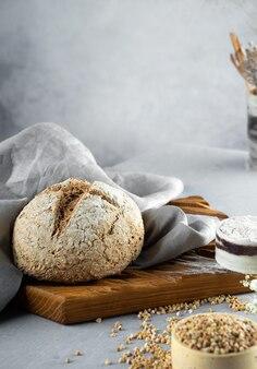 Chleb krzyżowy. domowy bochenek świeżo upieczonego zielonego chleba gryczanego leży na drewnianej desce kuchennej z szarą lnianą serwetką.bezglutenowy zdrowy wypiek dla wegan i wegetarian.alternatywny chleb