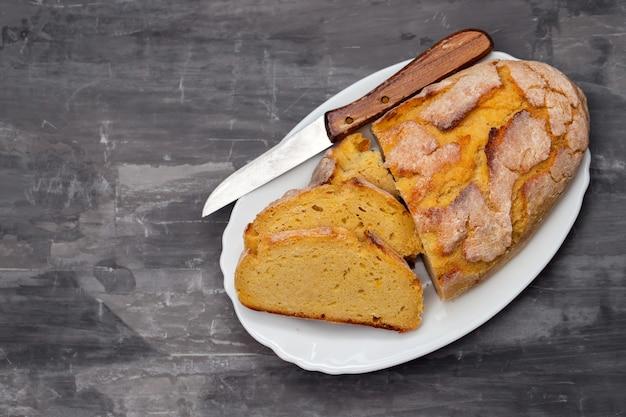 Chleb kukurydziany z nożem na białym naczyniu