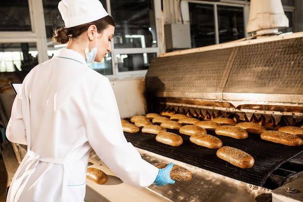 Chleb. linia do produkcji chleba. kobieta w mundurze. kontrola sanitarna.