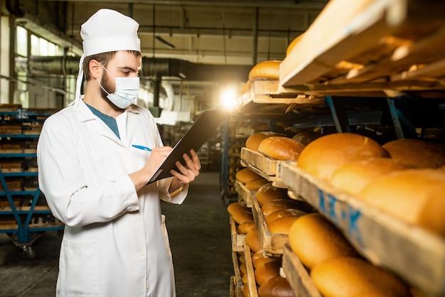 Chleb. linia do produkcji chleba. mężczyzna w mundurze. kontrola sanitarna.