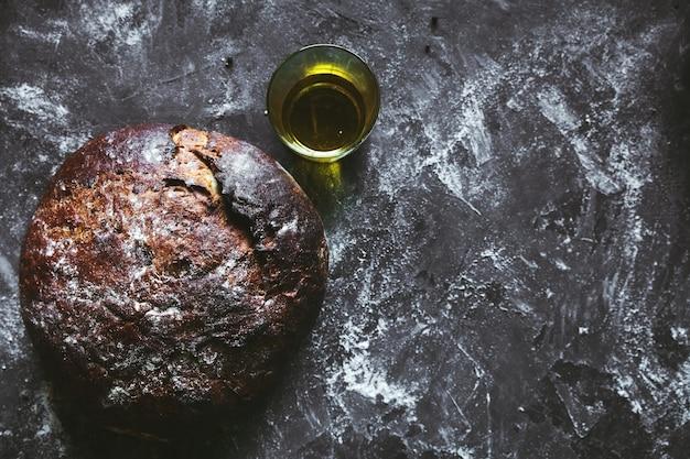 Chleb na czarnym tle z mąką i olejem. chleb leży na ręczniku. domowe jedzenie