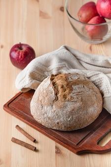 Chleb na stole z drewna. czerwone jabłka. kompozycja w stylu wiejskim.