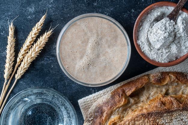 Chleb na zakwasie bez drożdży, mąka, woda i szklany słoik z zakwasem na stole. przygotowanie ciasta drożdżowego na chleb, bułki, ciasta lub pizzę, zbliżenie, widok z góry. proces gotowania