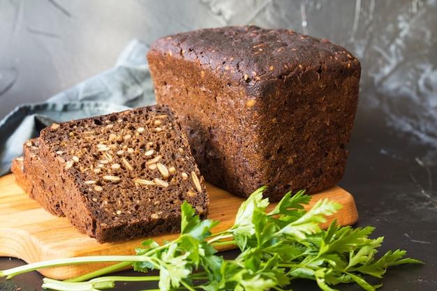 Chleb na zakwasie z pestkami dyni, na desce do krojenia i kromkach chleba
