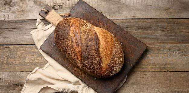 Chleb owalny pieczony w całości na brązowej desce do krojenia, widok z góry