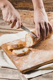 Chleb pełnoziarnisty nakładany na drewniany talerz kuchenny z szefem kuchni trzymającym złoty nóż do krojenia.