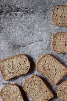 Chleb pełnoziarnisty w plasterkach na ciemnym tle rustykalnym drewniane, bio składniki, zdrowa żywność, widok z góry.