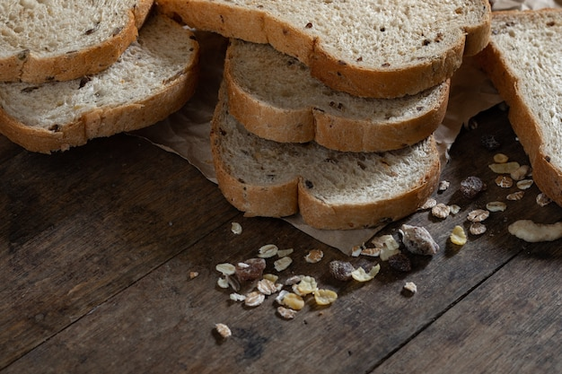 Chleb pełnoziarnisty w plasterkach na ciemnym tle rustykalnym drewniane, bio składniki, zdrowa żywność.