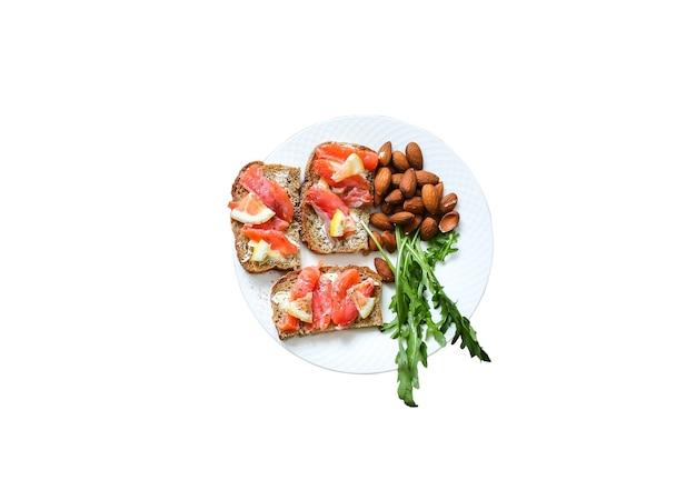Chleb pełnoziarnisty z łososiem na białym tle. rukola i migdał z cytryną. zdrowe kanapki. omega-3 na przekąskę. odpowiednie odżywianie. jedzenie sportowe.