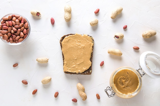 Chleb pełnoziarnisty z pastą orzechową z orzeszkami ziemnymi. jedzenie wegańskie. leżał płasko. widok z góry.