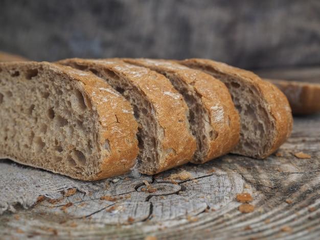Chleb pszenny żytni pokrojony na drewnianej desce