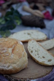 Chleb rzemieślnik pokrojony w plastry na obrusie w ogrodzie