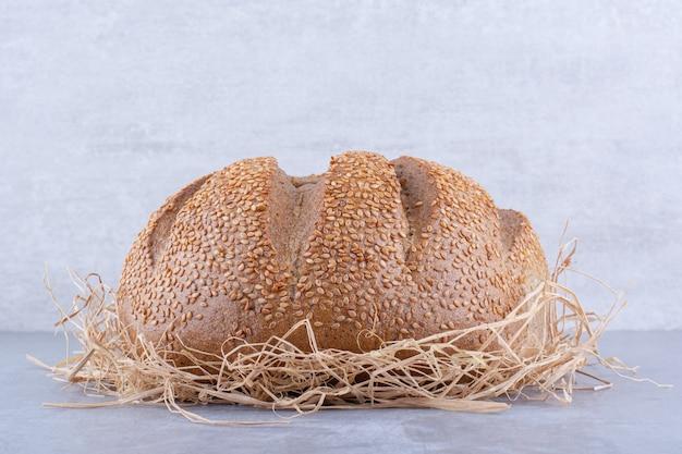 Chleb siedzi na stosie słomy na powierzchni marmuru
