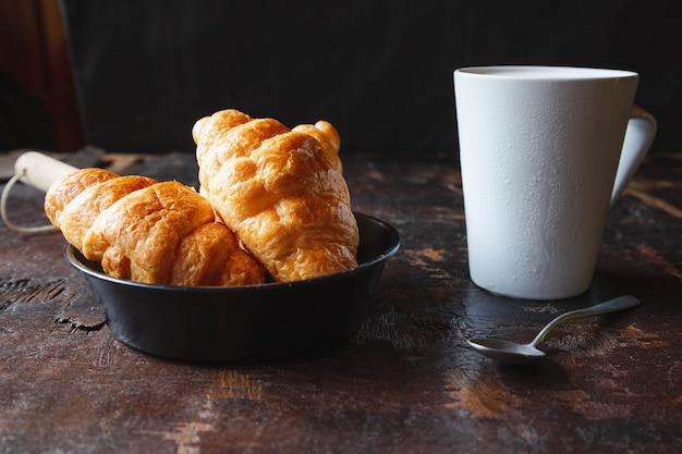 Chleb śniadaniowy, rogaliki i świeże mleko na drewnianym stole.