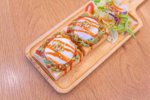 Chleb, sos z awokado, bekon, szpinak, jajko po benedyktyńsku na białym talerzu i tle starego drewna, sos awokado z połączeniem awokado i pomidorów, śniadanie