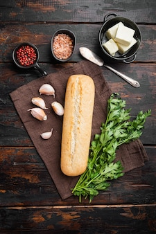 Chleb tostowy bagietka z zestawem składników czosnku i ziół, na starym ciemnym drewnianym stole tle, widok z góry płaski lay
