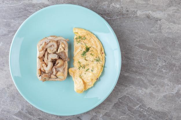 Chleb tostowy i omlet na niebieskim talerzu.