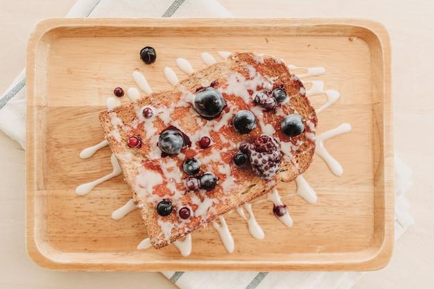 Chleb tostowy z jagodami ze skondensowanym mlekiem na drewnianym talerzu