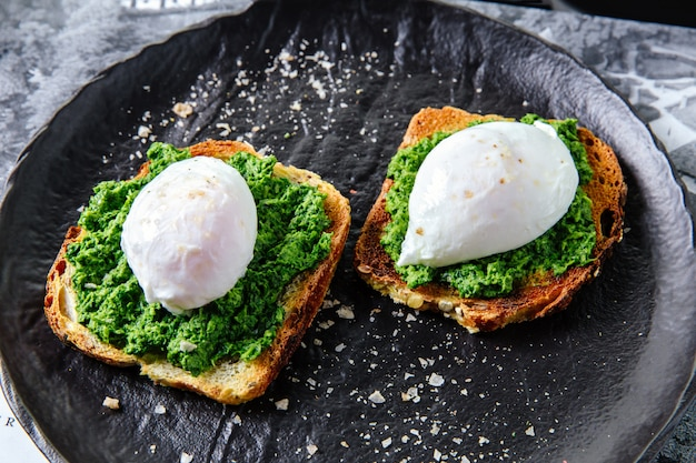 Chleb tostowy z jajkiem w koszulce i zieleniną