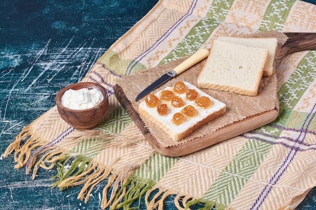 Chleb tostowy z konfiturą wiśniową i jogurtem.