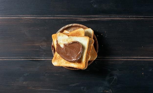 Chleb tostowy z kremem czekoladowym na rustykalnym drewnianym stole kuchennym, widok z góry