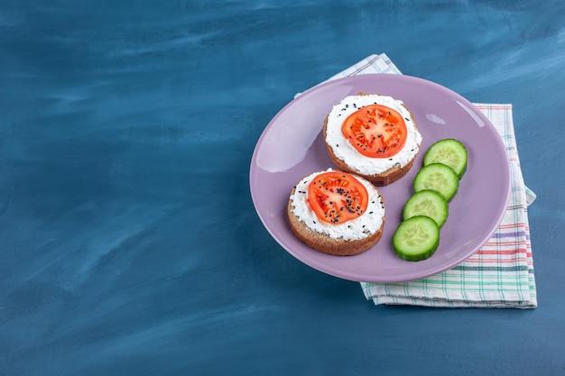 Chleb tostowy ze śmietaną i pokrojonymi warzywami na fioletowym talerzu.