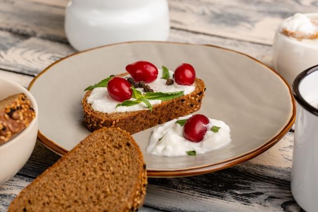 Chleb tostowy ze śmietaną wewnątrz talerza na szaro