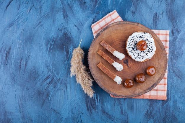 Chleb tostowy żytni ze śmietaną i konfiturą jagodową na kawałku drewna.