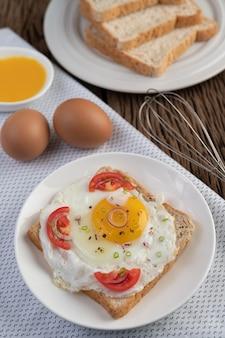 Chleb ułożony z jajkiem sadzonym z pomidorami, mąką z tapioki i pokrojoną dymką.