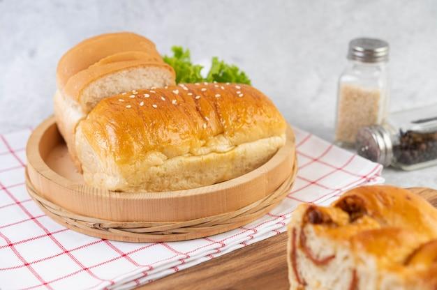 Chleb w drewnianej tacy na czerwono-białej tkaninie.