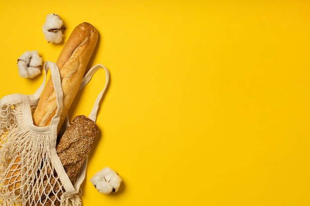 Chleb w ekologicznej bawełnianej torbie na żółtym tle
