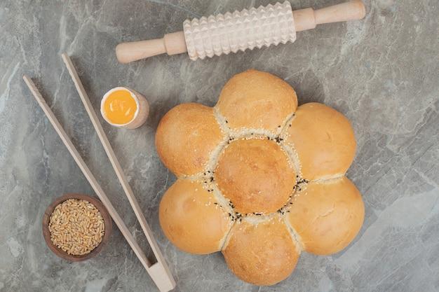 Chleb w kształcie kwiatu z jęczmieniem i narzędziami na marmurowej powierzchni. wysokiej jakości zdjęcie