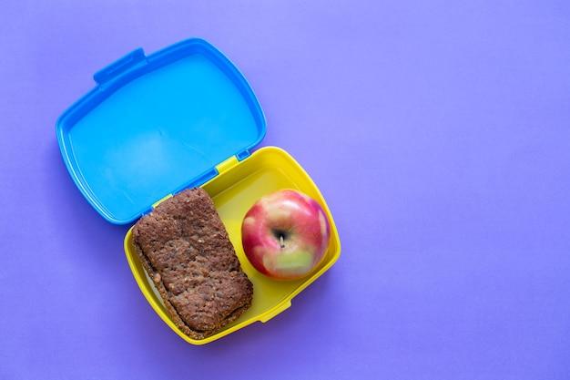 Chleb w pudełku z jabłkiem w jasnym kolorze
