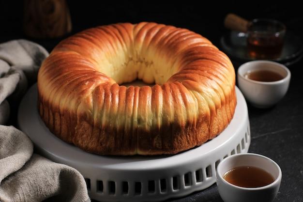 Chleb wełniany to słodkie ciasto chlebowe w kształcie kropelki wełnianej nici. nadziewane czekoladą i tartym serem. podawane w białym talerzu, czarny stół