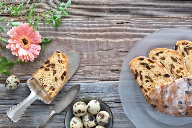 Chleb wielkanocny (osterbrot po niemiecku). odgórny widok tradycyjny fruty chleb na nieociosanym drewnie z świeżymi liśćmi i przepiórek jajkami.